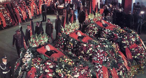 Imagen del funeral que muestra los tres ataúdes cubiertos de flores.