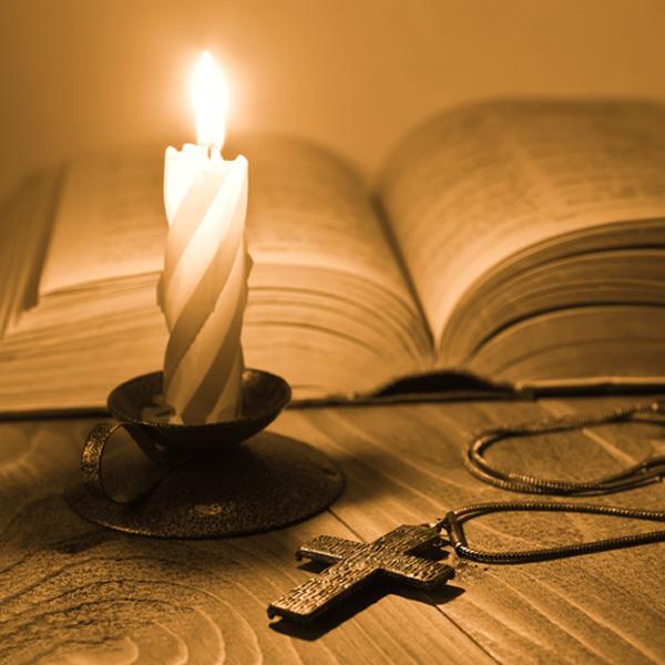 Imagen de una biblia abierta, a la luz de una vela, con un crucifijo al pie.