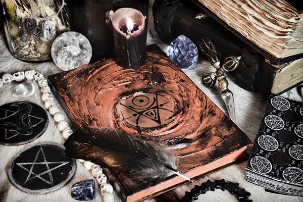 Libro esotérico en medio de lo que aparenta ser un altar de rituales paganos.