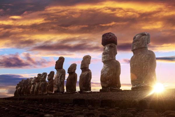 Imagen de esculturas ancestrales conocidas como moáis, de pie en Isla de Pascua contra el sol naciente y el cielo naranja.