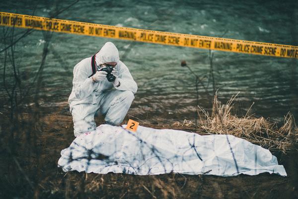 Fotógrafo, tomando fotos de la escena del crimen por el río.