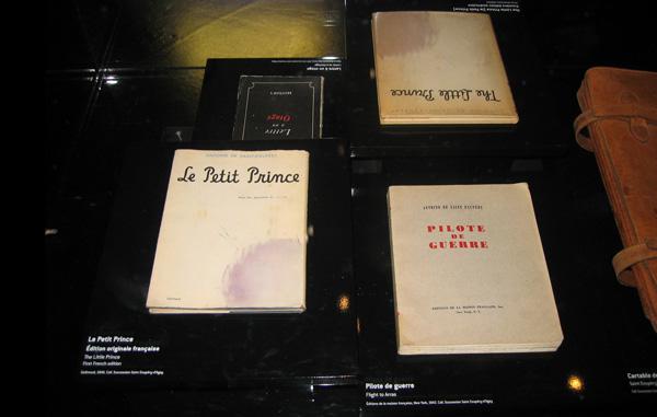 Se muestran cuatro títulos de las obras de Saint-Exupéry: Le Petit Prince (abajo a la izquierda), El Principito (arriba a la derecha), Pilot de Guerre (abajo a la derecha) y Lettre à un otage (arriba a la izquierda).