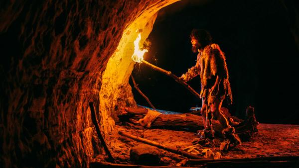 Hombre de las cavernas explora una cueva con antorcha en mano.
