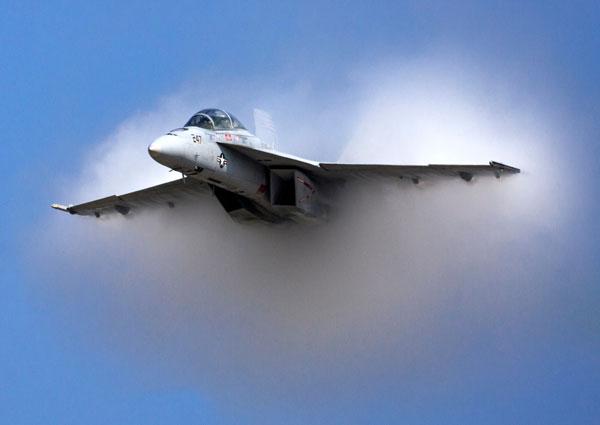 Avión volando en el cielo cruza una nube.
