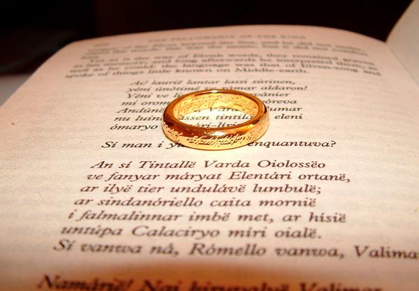Página del libro La comunidad del anillo junto con una réplica del Anillo Único en medio.