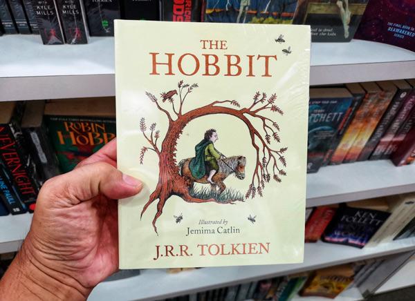 Mano sosteniendo el libro El Hobbit en venta en la librería.