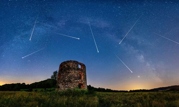 Lluvia de estrellas y la Vía Láctea sobre una ruina vieja.