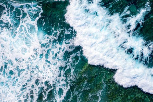 Olas ásperas del mar salpicando cerca de un fondo marino rocoso.