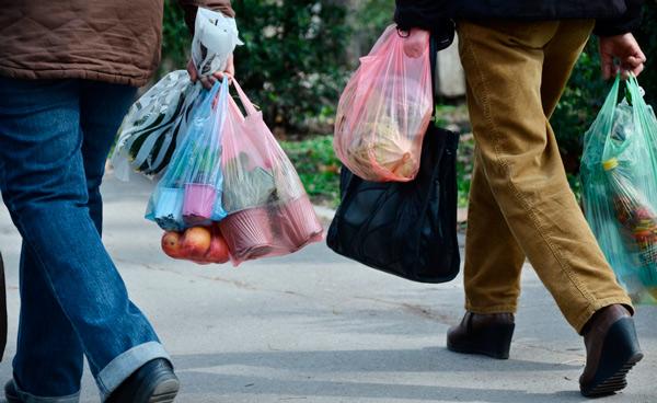 Personas llevando bolsas de compras de plástico.