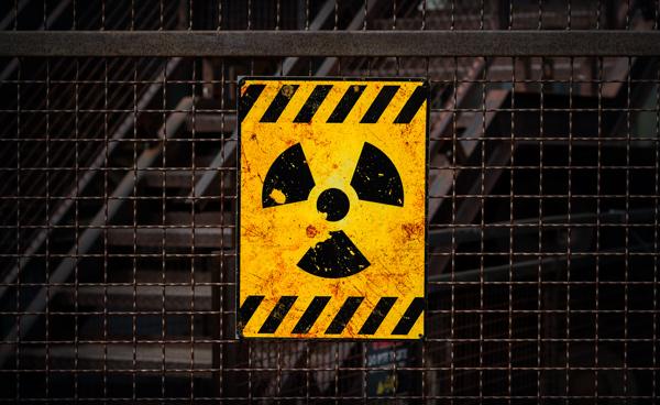 Cartel de peligro radioactividad sobre un perímetro enrejado.
